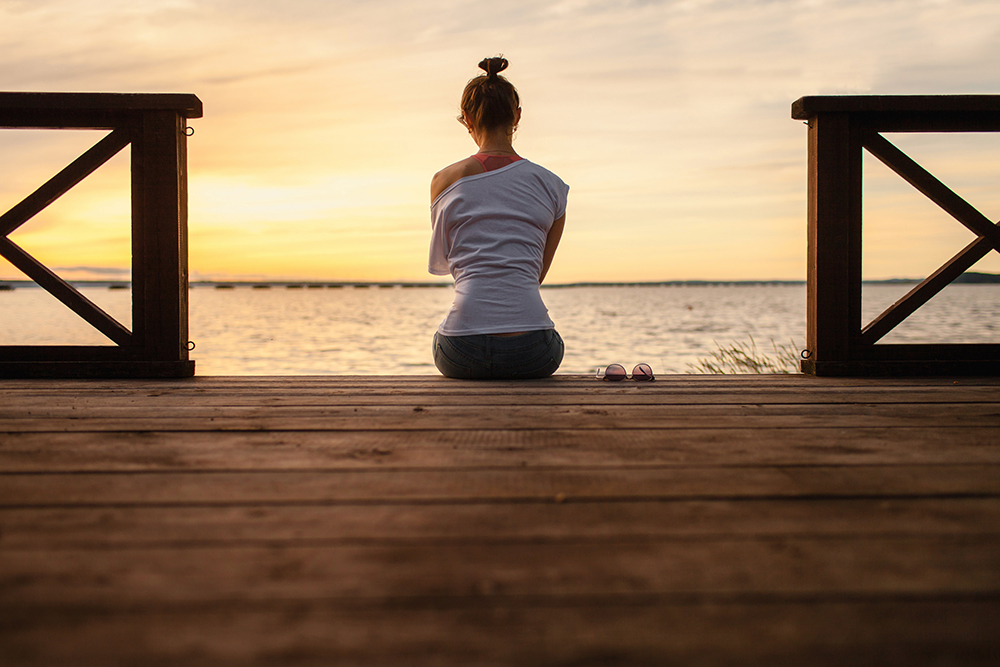 a young woman sitting on a dock looking at a lake