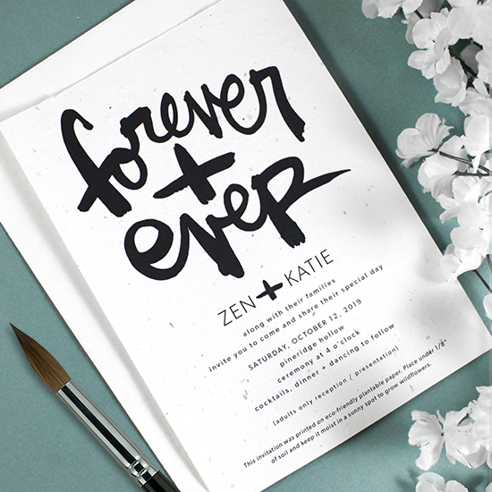 With beautiful, bold brush script artwork by artist Kal Barteski, these plantable wedding invitations feature the words FOREVER + EVER.
