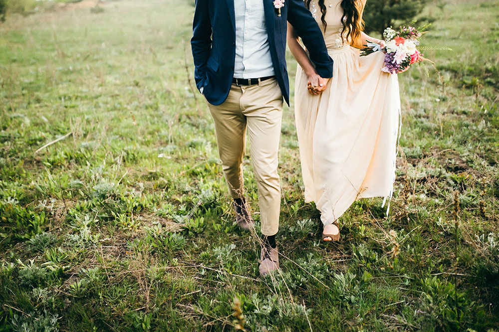 bride and groom running through a field