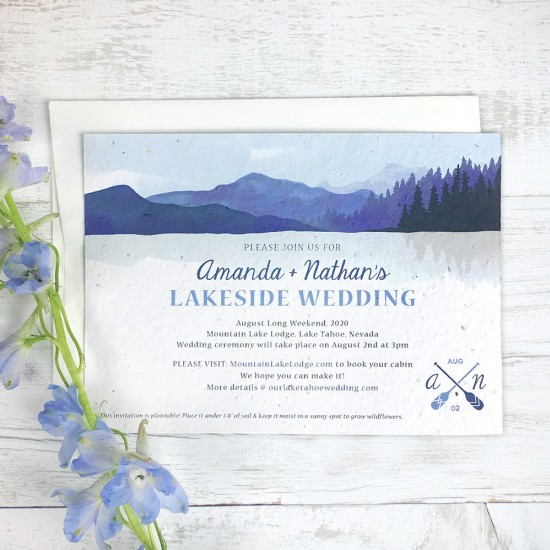 Perfect for rustic lakeside weddings, these artistic plantable wedding invitations capture a serene spot with rolling hills, trees, and calm waters.
