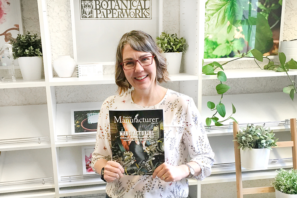 Heidi Reimer Epp holding a copy of Prairie Manufacturer Magazine