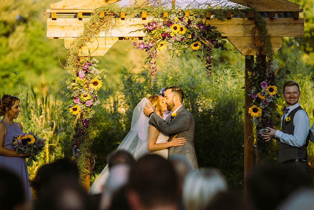 bride and groom kissing at the altar