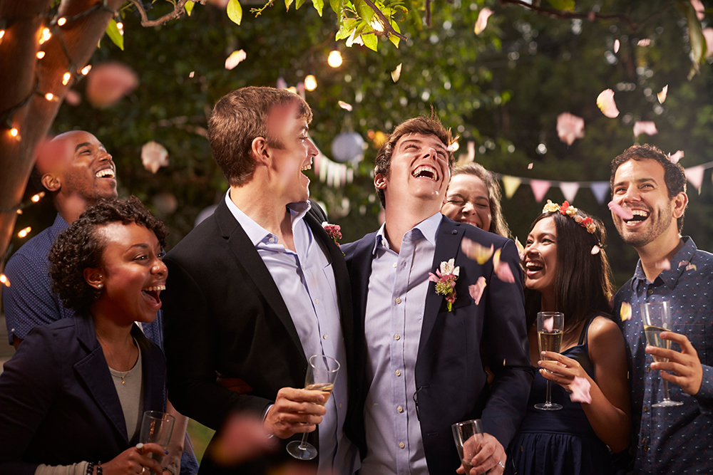 two grooms at their wedding with rose petals