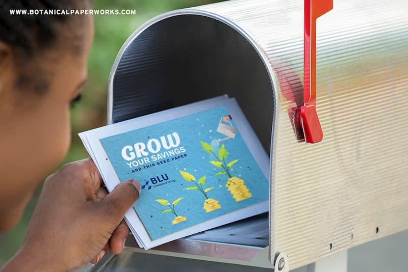 A girl putting a seed paper card in a mailbox