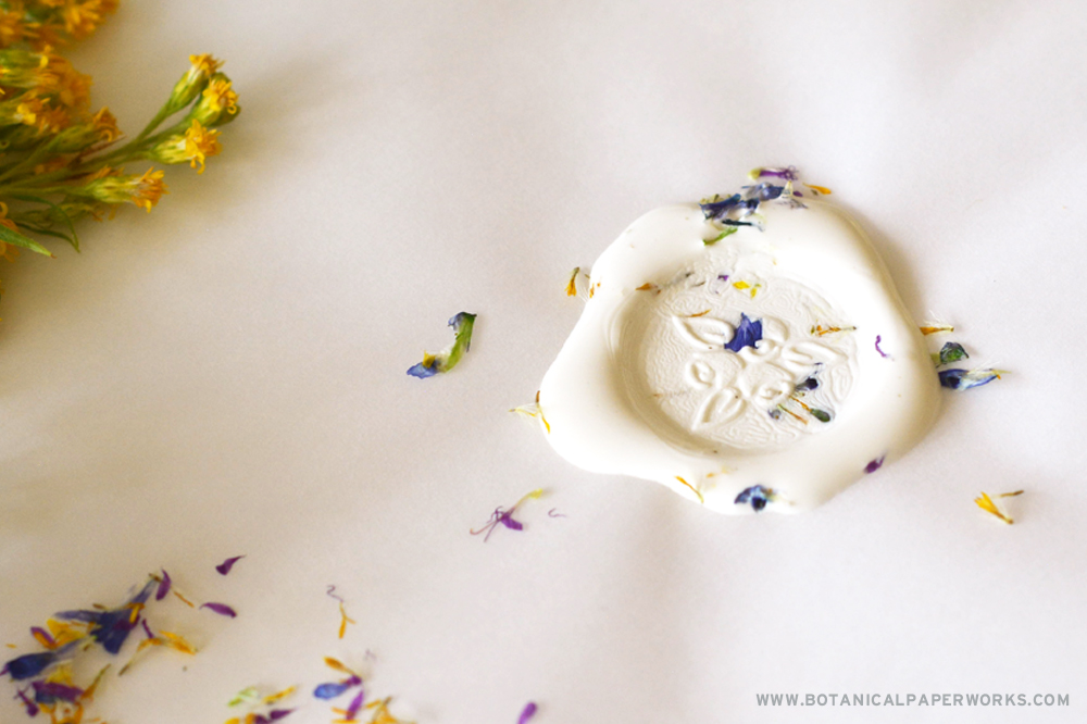 Close-up of a wax seal with dried flowers