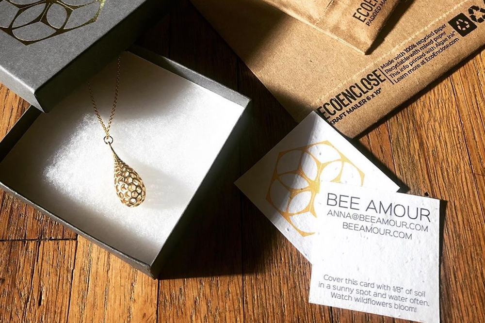 bee amour jewelry company's wildflower-seed embedded seed paper business cards and tags with a honeycomb-inspired necklace