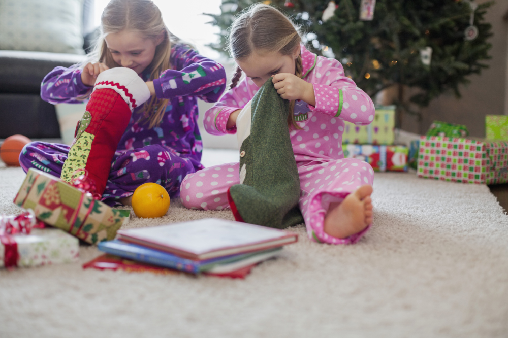 two little girls looking into their christmas stockings