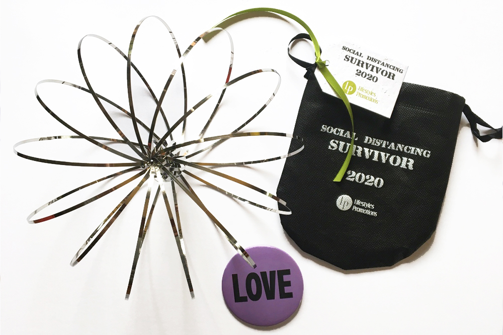 Lifestyles Promotions social distancing survivor kits including a 'Love' pin and plantable seed paper tag.
