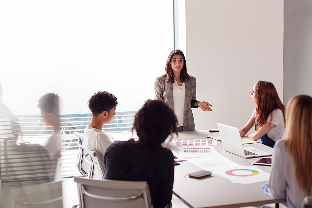 5 business women in a meeting around a white table