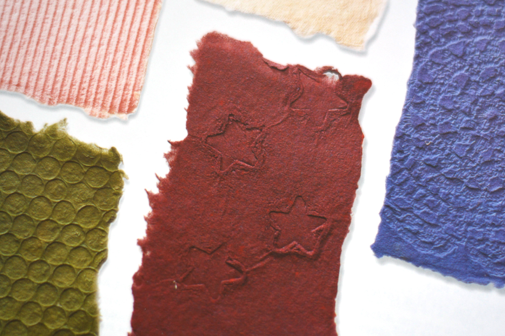 sheets of fabric-embossed paper with bubble wrap, clothing, and doily impressions.