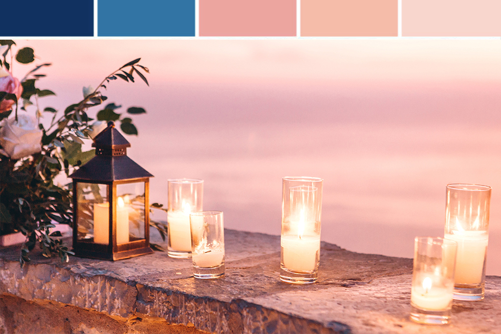 Candles on a stone fence at dusk with color palette for garden wedding inspiration.