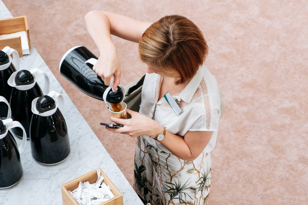 a woman pouring herself a cup of coffee