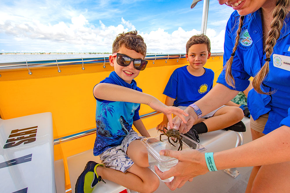 kids learning about Tampa Bay marine life with a tour guide who is wearing a seed paper wristband