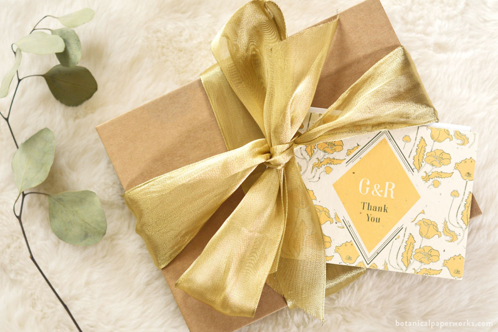 a diy wedding welcome box wrapped in a gold ribbon, packaged in a kraft frame box, and topped with a seed paper thank you card.