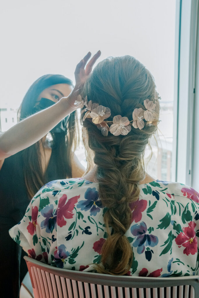 a makeup artist and bride wearing a floral headband for her wedding
