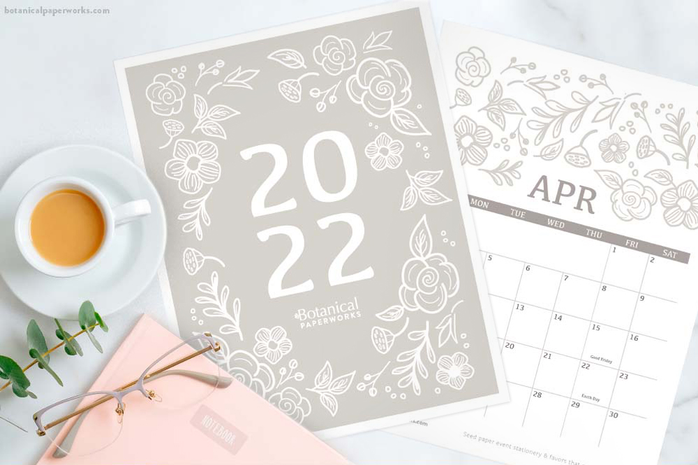 a free printable 2022 calendar with a modern botanical print on a beige background with coffee and a pink notebook