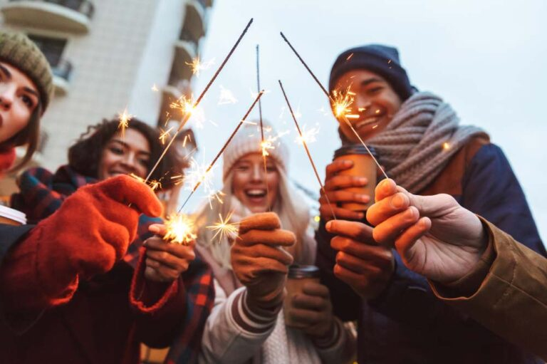a group of friends lighting sparklers during the holidays