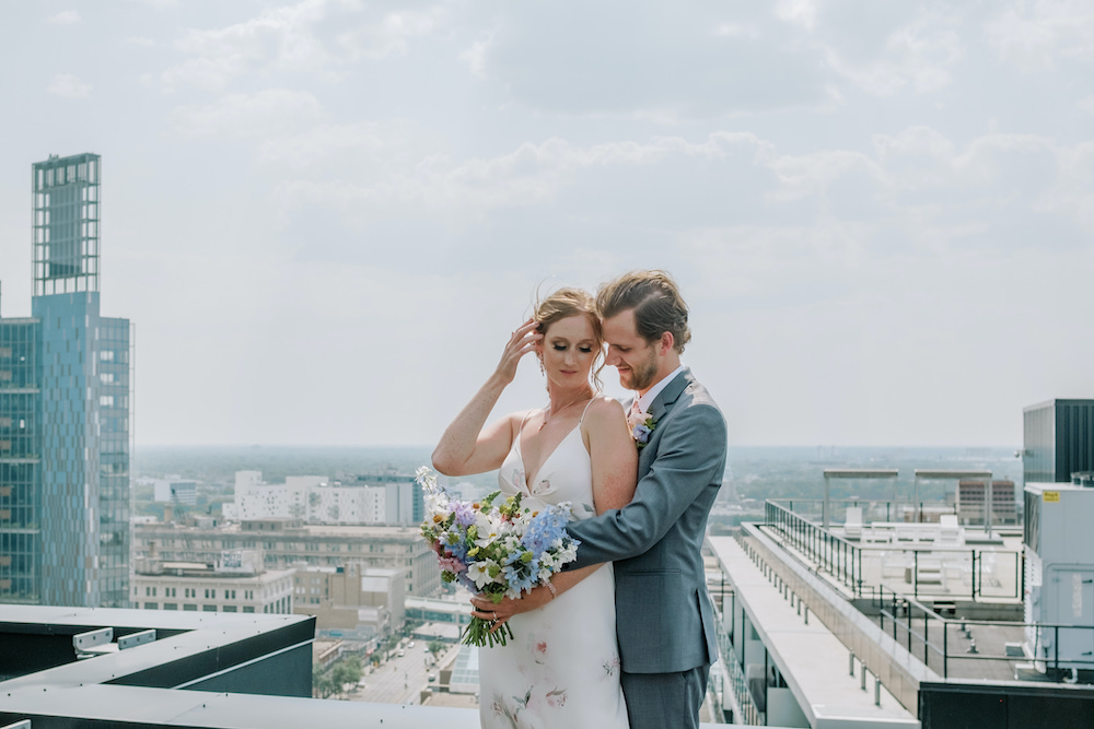 a bride and groom posing for a wedding photo on a hotel rooftop with a cityscape as the backdrop
