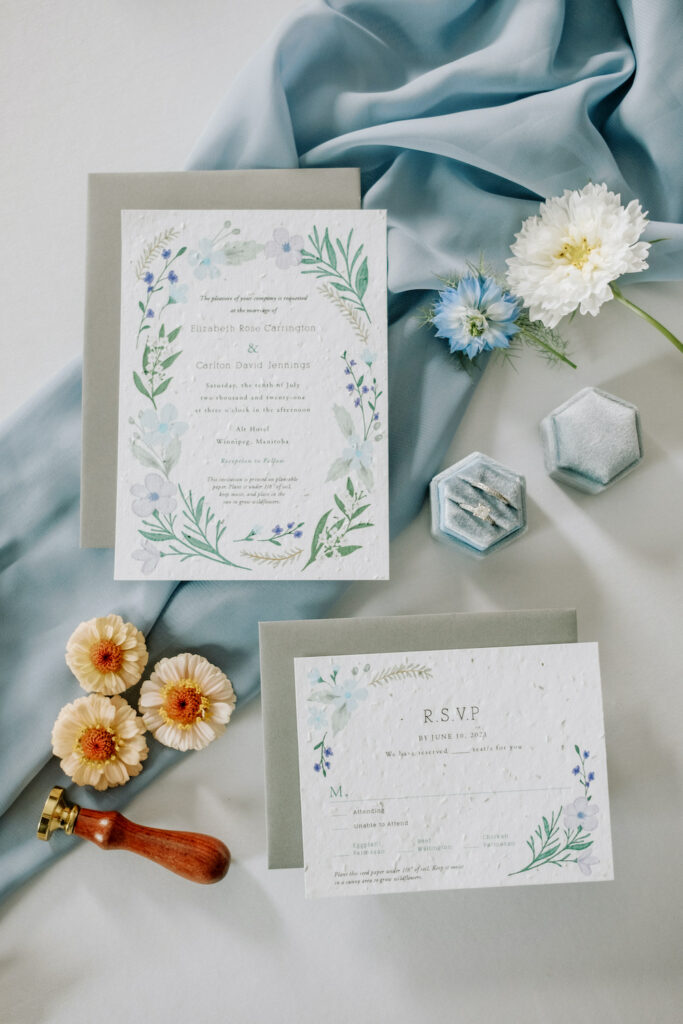 a flatlay of wildflower plantable wedding invitations and reply cards, with light blue fabric, wedding ring flowers and wax seal stamp