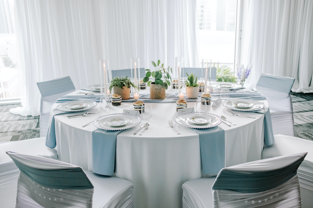 a wedding table with light blue napkins, silver chairs, and potted plants as centerpieces