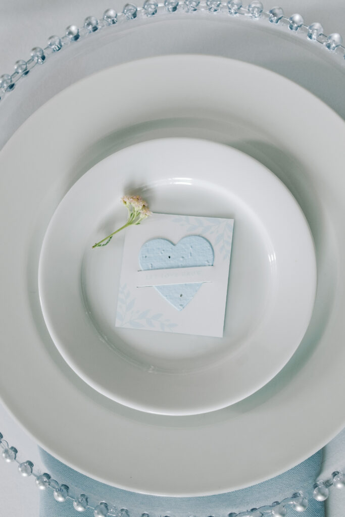a plantable seed paper heart mini slot card wedding favor in light blue with a sprig of wildflowers
