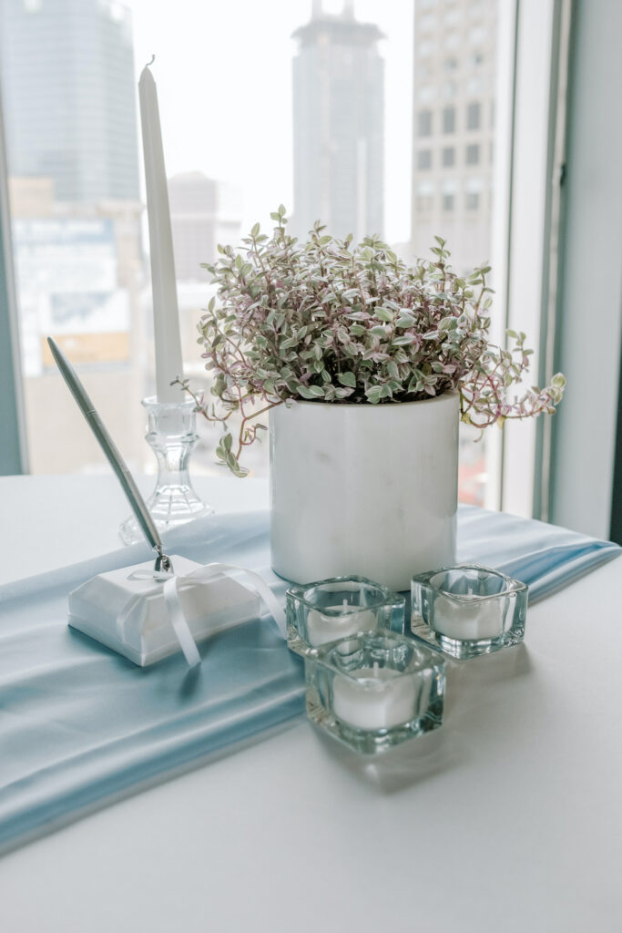 a wedding signage table with a potted plant, tea light candles, a signing pen, and candlestick