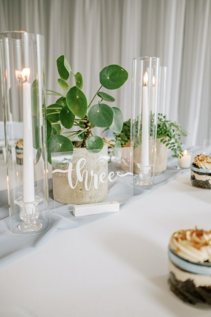 a glass wedding table number next to potted plants and cupcakes