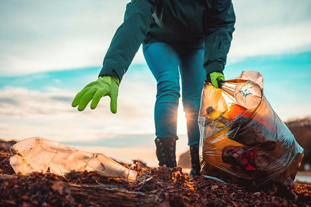 a person picking up trash with bright green gloves