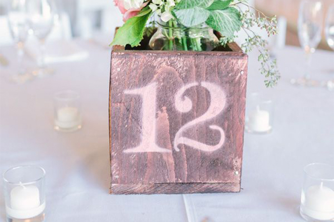 Spray paint your DIY table numbers onto old wooden flower boxes for a centerpiece and table number in one.