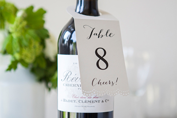 Attach your DIY table numbers to a bottle of wine for an elegant look that is simple and classic.