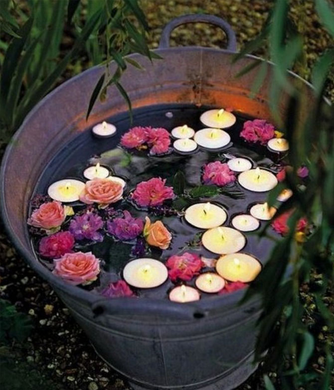 This bucket with flowers and candles is a romantic addition to a garden party wedding.