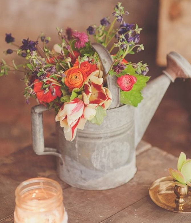 Watering can accents with floral arrangements for a garden party.