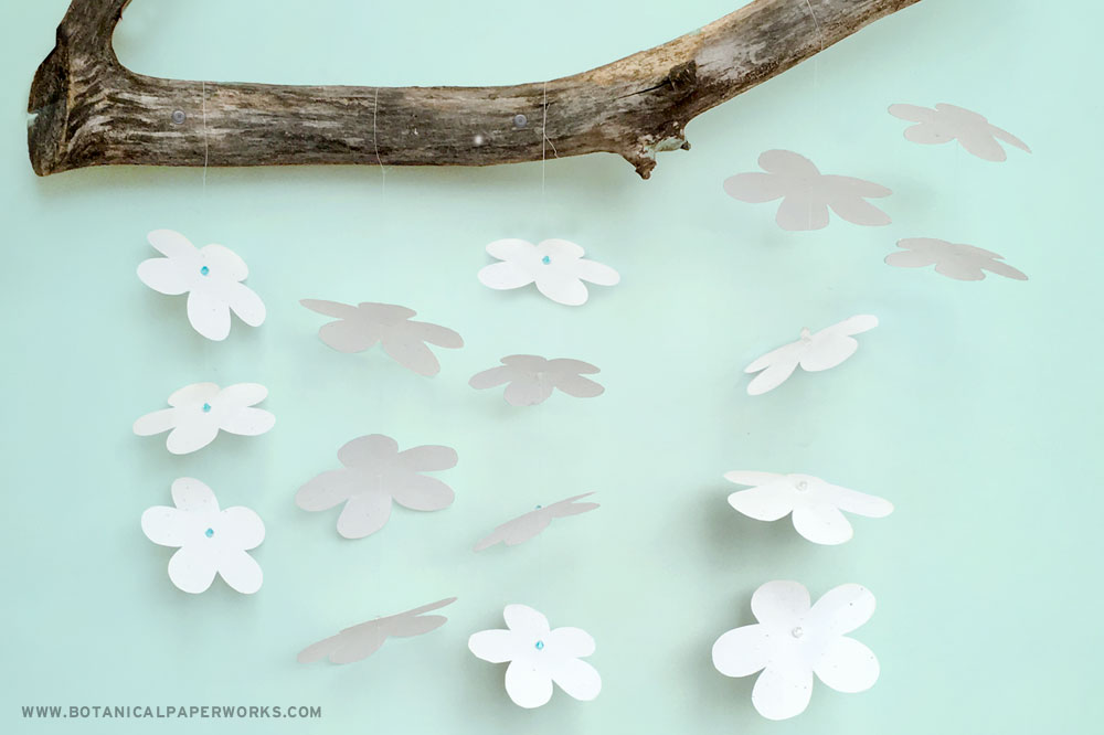 seed paper flowers hanging from a branch