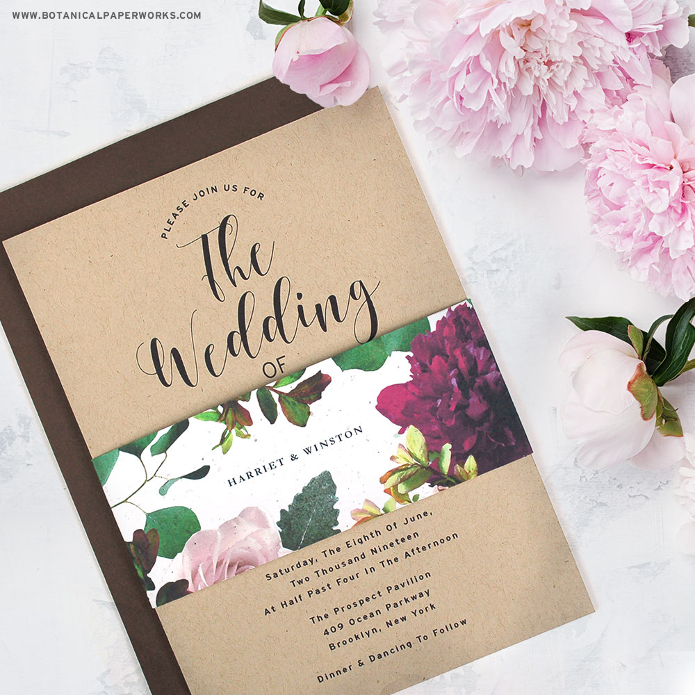 Calligraphy-based kraft paper invitations with a colorful blooming seed paper belly band.