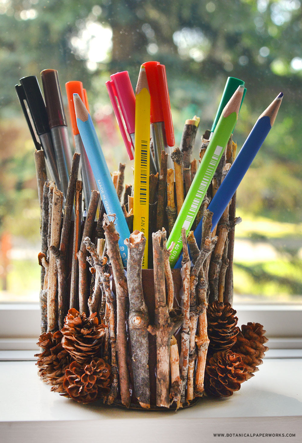 Bring a touch of the outdoors into your workspace with this eco-friendly craft project that uses toilet paper rolls and twigs.