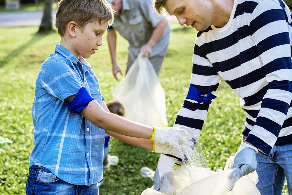 a young boy picking up garbage