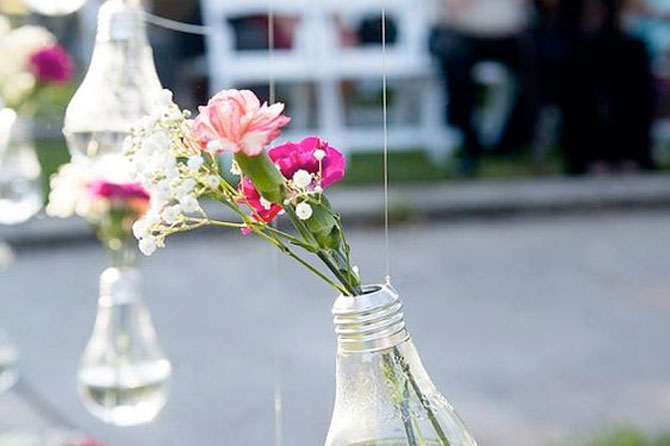 Repurpose light bulbs into hanging vases for eco-friendly weddings.